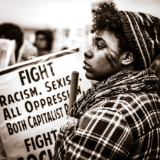 A young black woman with protesters, Washington D.C., 2017.