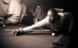 Young black man playing pool.